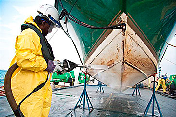 worker cleaning a ship hull by blasting with dry ice