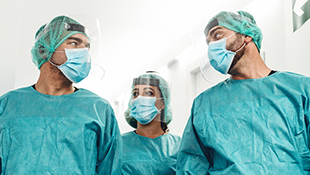 Three healthcare workers wearing surgical masks, face shields and surgical scrubs walk down a hospital hallway.