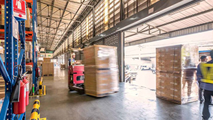 A blurry pallet of boxes on a lift moves through a warehouse.