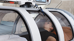 A woman lies inside a hyperbaric chamber.