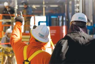 Set in an industrial warehouse, plant or facility, two men walk through the facility (with backs turned to camera) wearing personal protective equipment (PPE): Airgas branded hardhats.