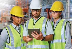 Set in an industrial facility, three people, two women and a man, stand together looking at a tablet computer. All wear personal protective equipment (PPE), including hardhats, safety glasses and high-visibility safety vest.