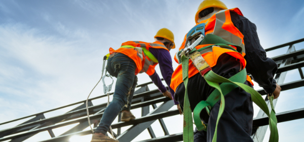 Two workers wearing safety harnesses and climbing