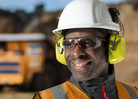 A worker wearing Honeywell Uvex safety glasses, protective earmuffs and a hardhat smiles on a jobsite.