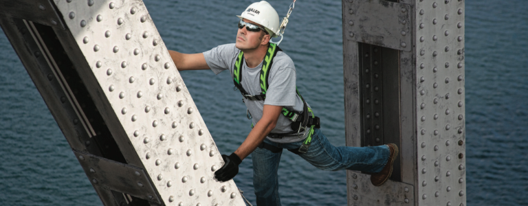 A worker wearing a Honeywell Miller fall-protection harness scales a beam.