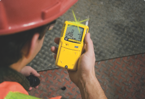 Mid-shot of a Honeywell BW Clip gas detector grasped in a worker's hand.