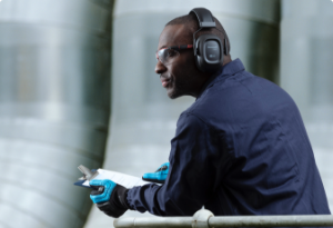 A worker wearing Honeywell protective earmuffs peers out over a balcony.