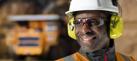 A worker wearing Honeywell Uvex safety glasses, earmuffs and a hardhat smiles on a jobsite.