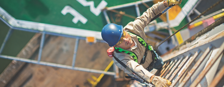 From a top-down view, a worker wearing a Honeywell Miller harness climbs a ladder.