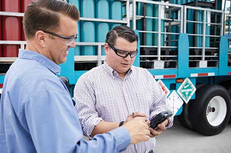 An Airgas driver delivering cylinders to a customer who is signing a digital proof of receipt (POD) on a handheld device.