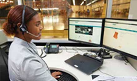 Set in a warehouse or distribution center, a smiling worker with a headset sits at a large desk and works at a computer displaying the Airgas.com homepage.