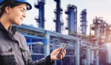 A refinery worker looking at her smartphone.