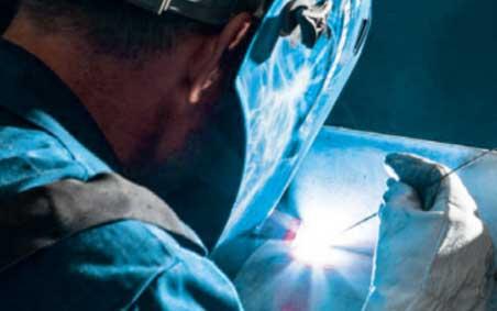 Welder, wearing welding helmet & welding gloves, TIG/GTAW welding with ARCAL Prime premium shielding gas.