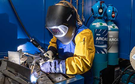 Welder welding with Arcal, EXELTOP, ARCAL Cylinders in the background.