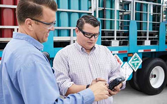 Delivering cylinders to a customer who is signing a digital proof of receipt on a handheld device.