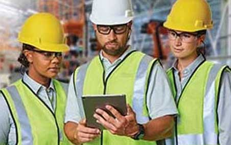 Two women and a man, stand together looking at a tablet. All wear personal protective equipment (PPE)