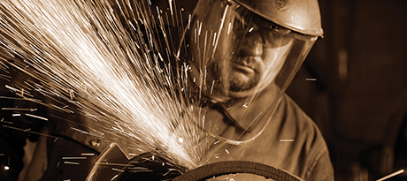 Sparks fly from a machine operated by a worker in 3M protective face gear.