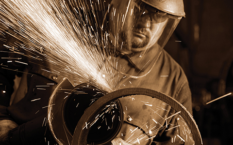 Sparks fly from a machine operated by a worker in protective face gear.