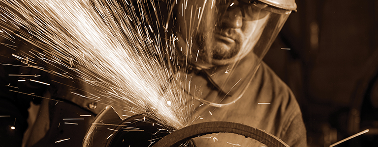 Sparks fly from a machine operated by a worker in protective face gear..