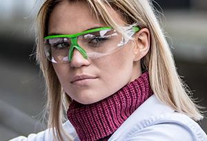 A female worker wears protective eye gear.