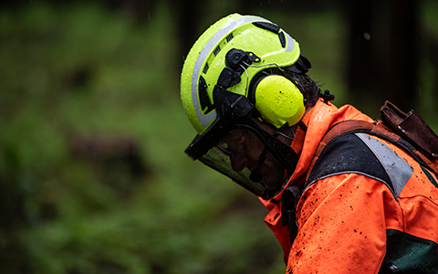 A worker with protective ear, face and head gear looks down at the job.