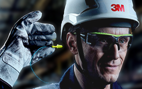 A worker with protective 3M eye and head gear and gloves places an earplug into his ear.