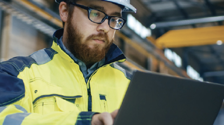 A man wearing personal protective equipment (PPE) in an industrial plant, warehouse or facility, types on a laptop computer.