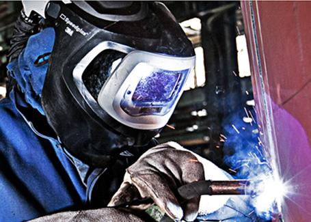 A worker wears a 3M welding helment on the job.