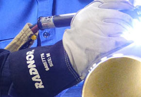 Close-up shot of welder's hands protected by RADNOR welding gloves.
