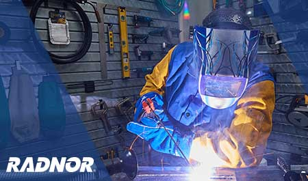 Welder using RADNOR welding tools and consumables, while wearing RADNOR welding helmet, welding jacket and welding gloves.