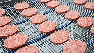 Frozen meat patties on a food production line; with title in upper left corner: Freezing and Chilling Food.