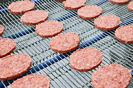 Multiple rows of meat patties on a food production line.