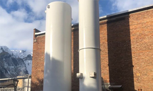 Two liquid nitrogen bulk tanks on the side of a brick building.