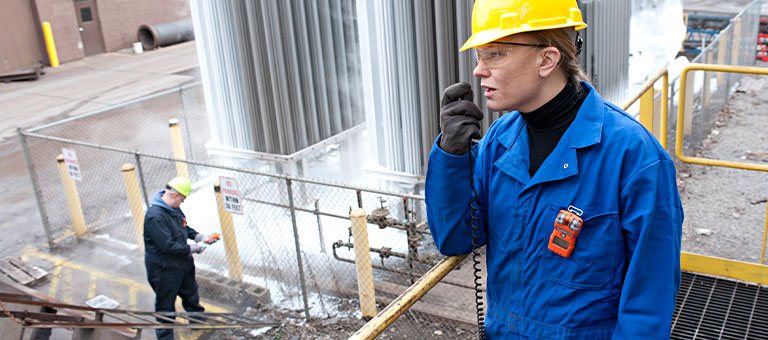 Woman on-site talking into 2-way radio wearing a hardhat, protective gloves, and a gas monitor clipped on the chest pocket of her coverall.